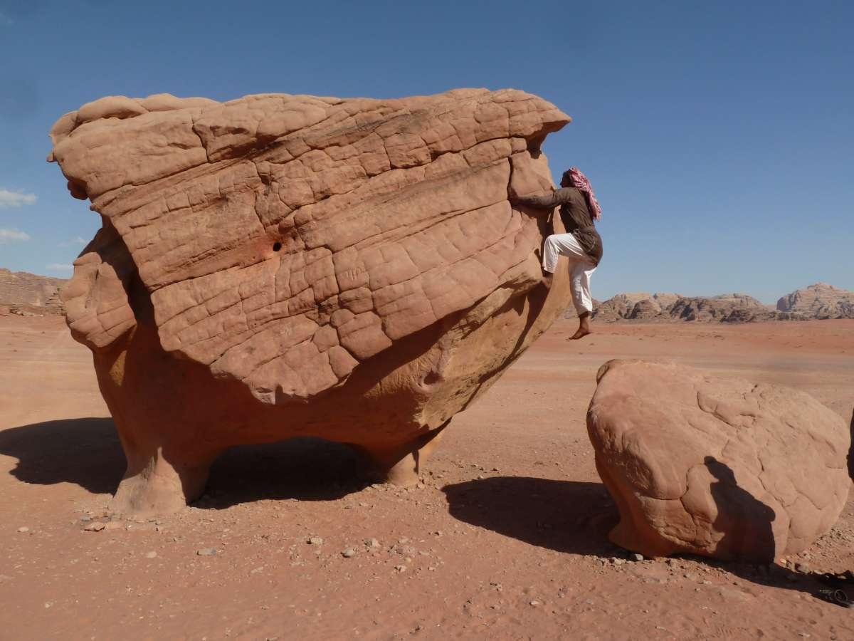 Beduine zieht sich am Fels hoch