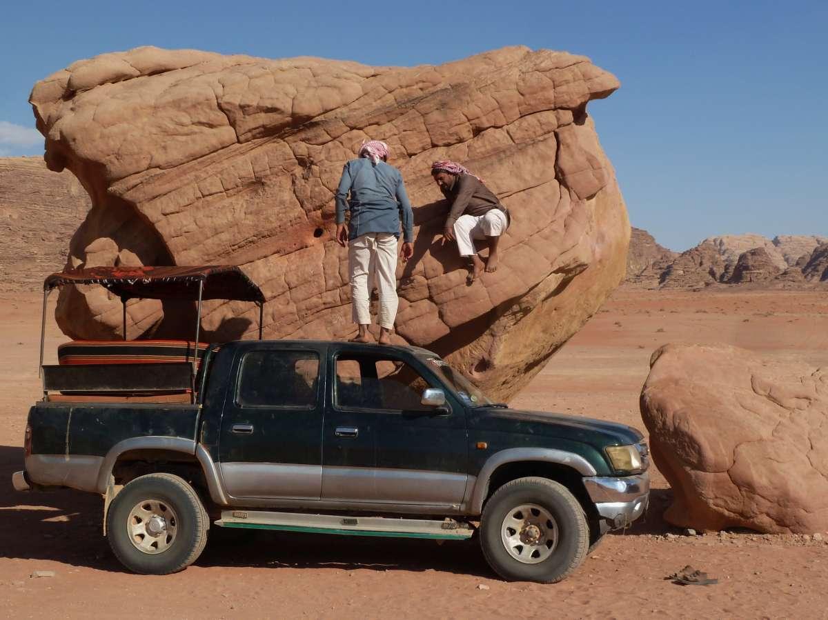 Beduine klettert vom Fels aufs Dach des Jeep