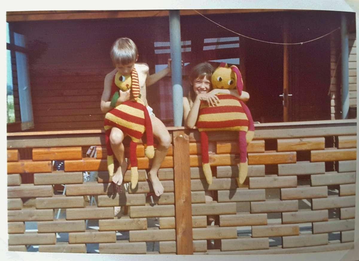 Zwei Kinder mit zwei rot-gelb geringelten Strickhasen