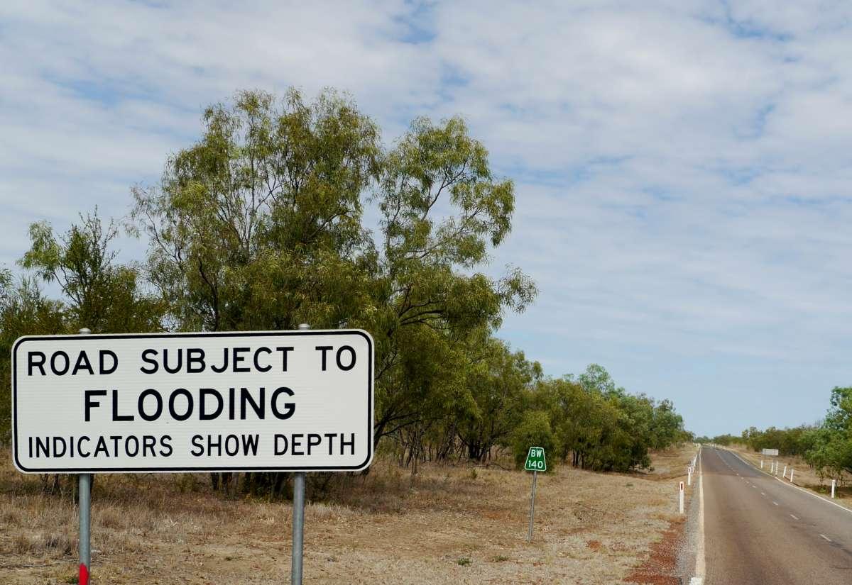 Schild, das vor Überflutung der Straße warnt