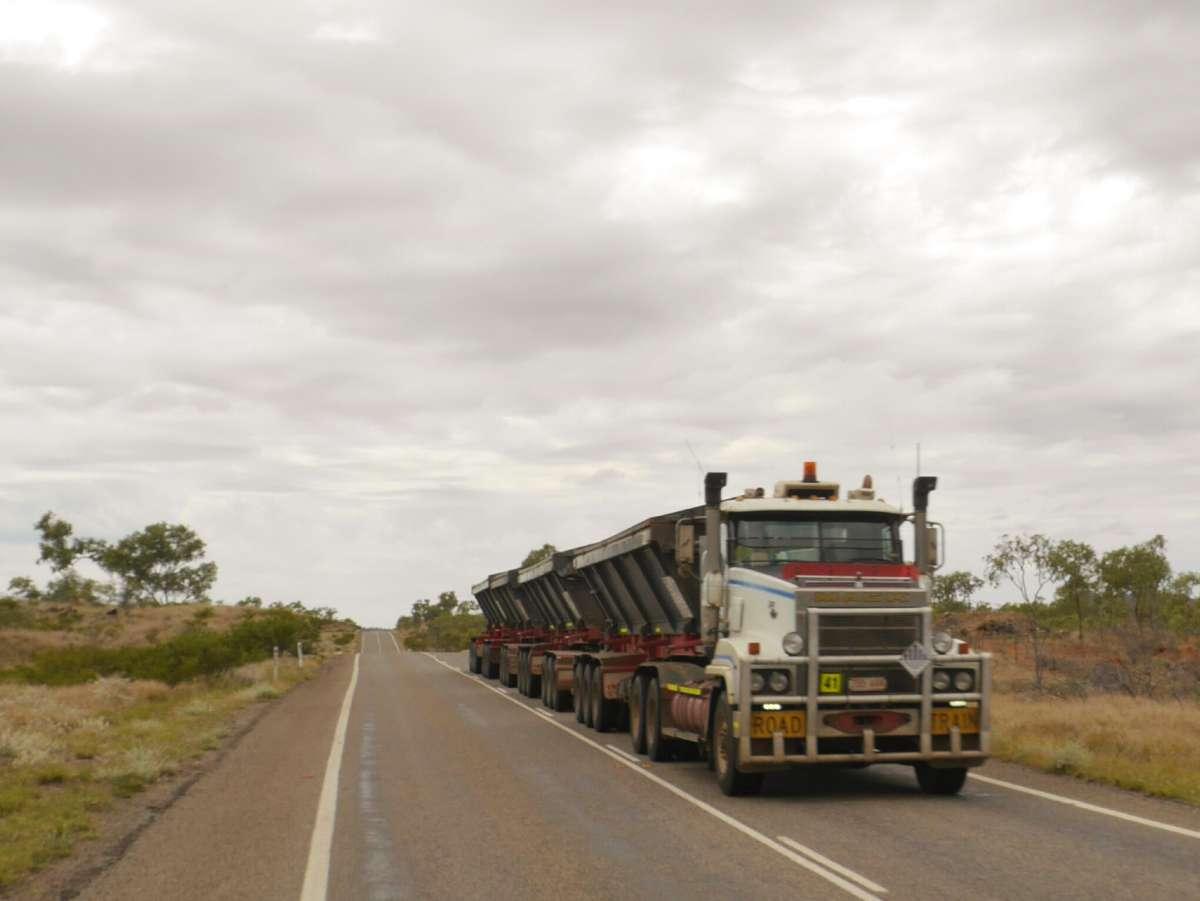 Roadtrain mit drei Anhängern kommt auf der Straße entgegen