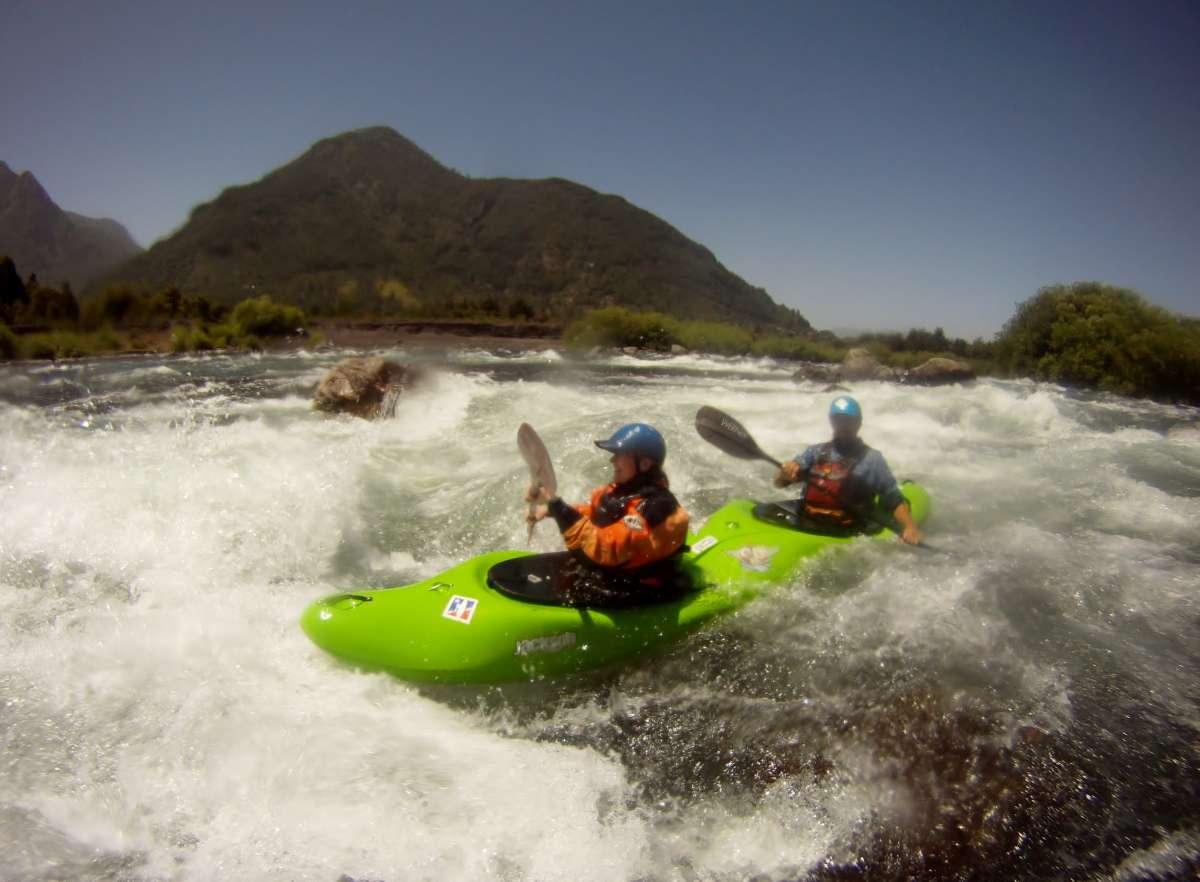 grünes Zweier-Kajak fährt durch die Wellen des Rio Liucura in Chile