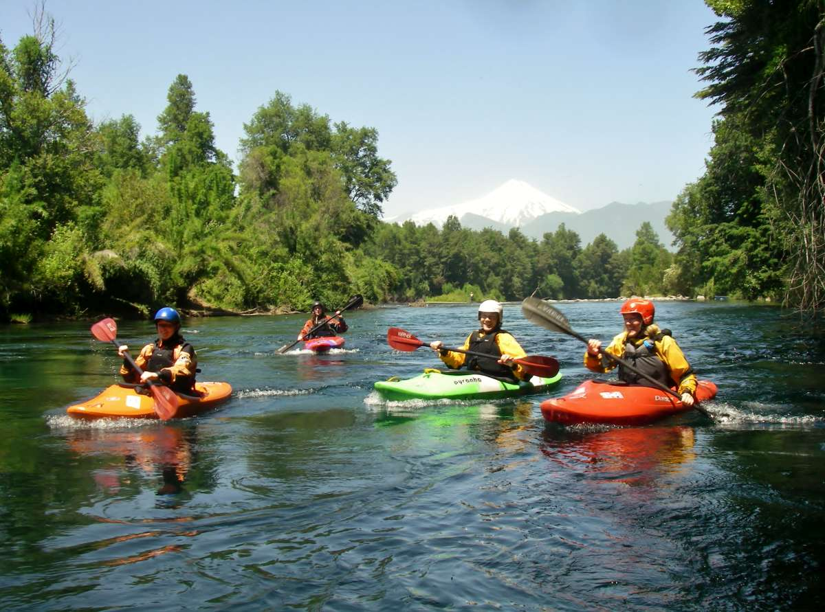 vier bunte Kajaks auf ruhigem Fluss in Chile