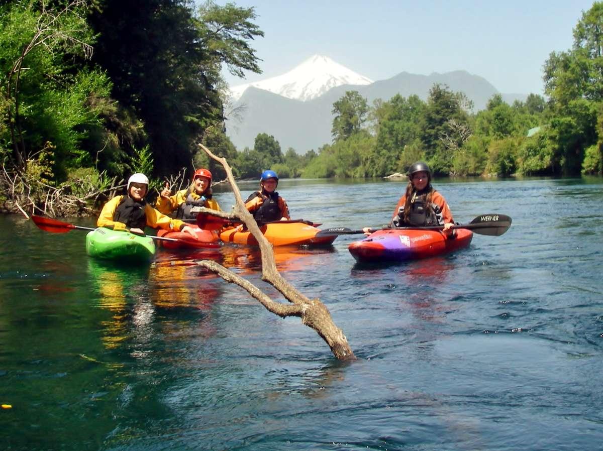 Vier Kajaks auf dem Fluss, im hintergrund der Vulkan