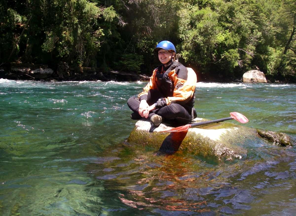Victoria sitzt auf einem Fels im Fluss Rio Liucura in Chile