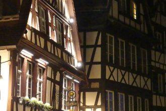 beleuchtete Fachwerkhäuser bei Nacht in Straßburg im Winter