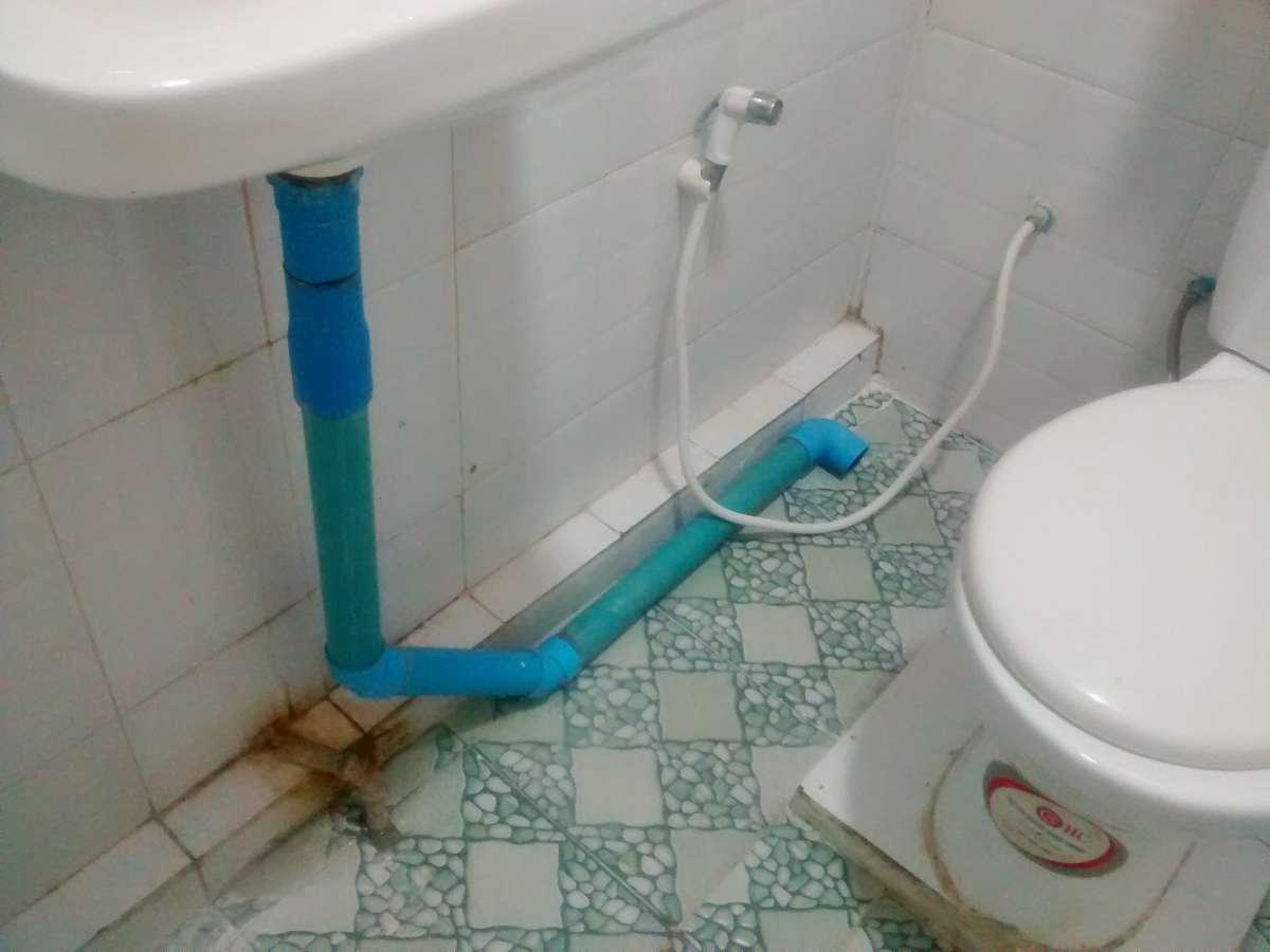 einfaches Bad. Der Abfluss des Waschbeckens läuft über den Boden ab.