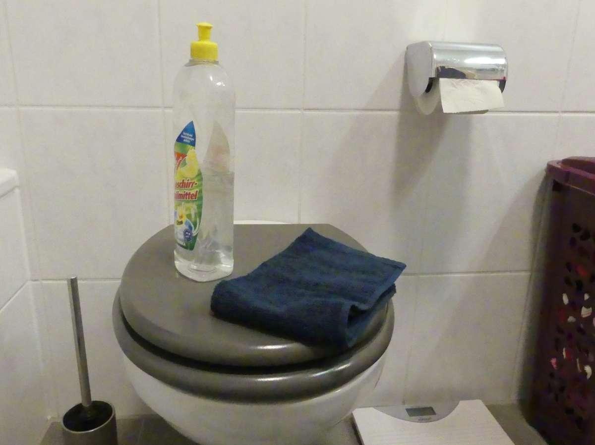 Spritzflasche mit Wasser und kleines Handtuch auf Klodeckel