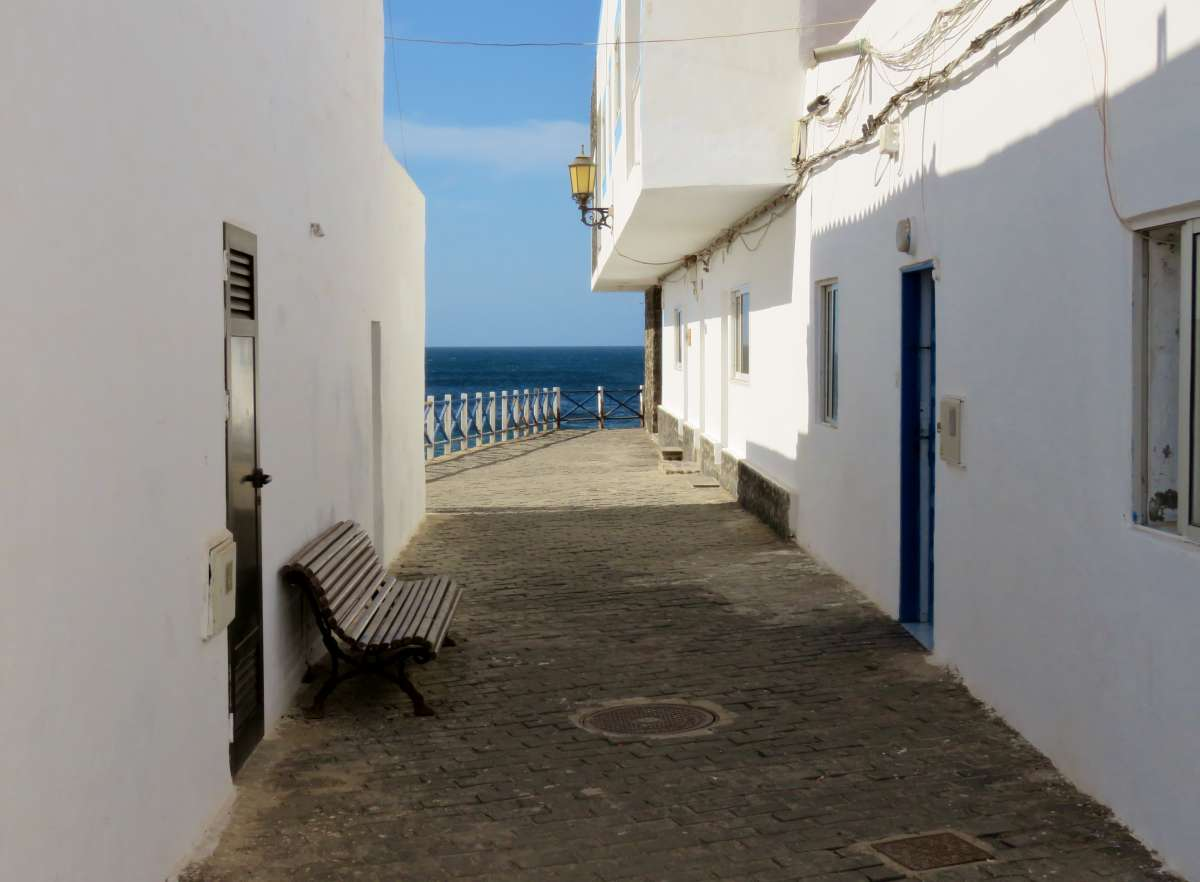 Gasse mit weißen Häusern und Blick aufs Meer