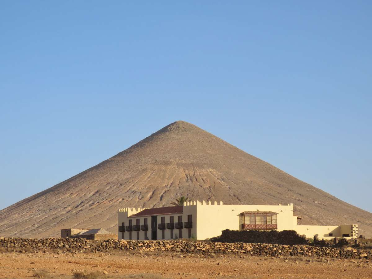 helles Herrenhaus vor Vulkan im Hintergrund
