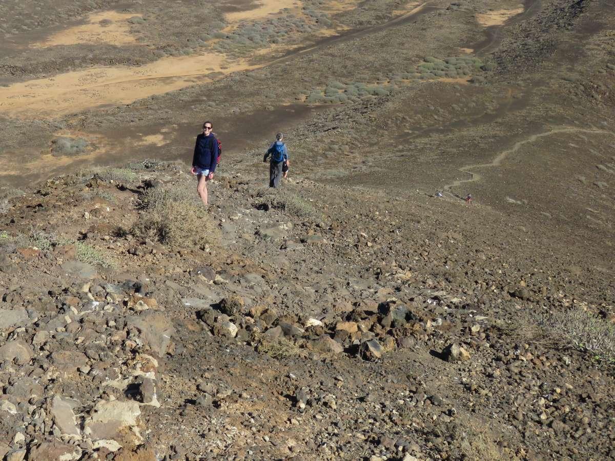 Zwei Personen steigen die Bergflanke hinab