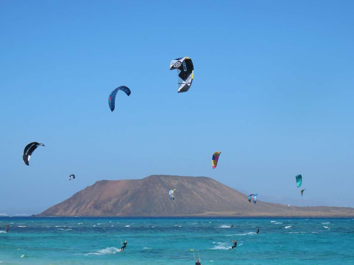 viele Kitesurfer auf türkisem Meer, im Hintergrund die Insel Lobos