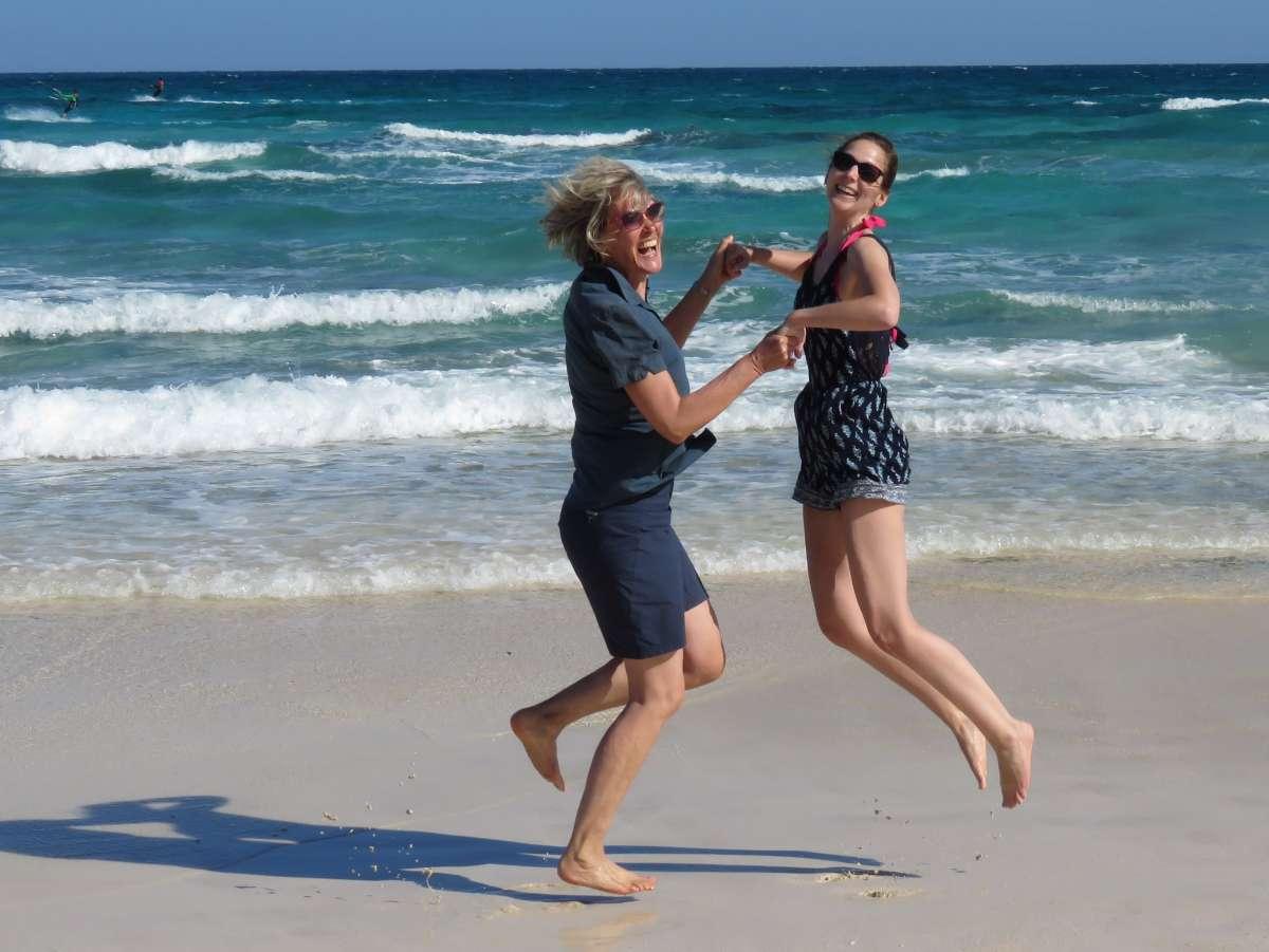 Gina und Jorina hüpfen am Strand in die Höhe