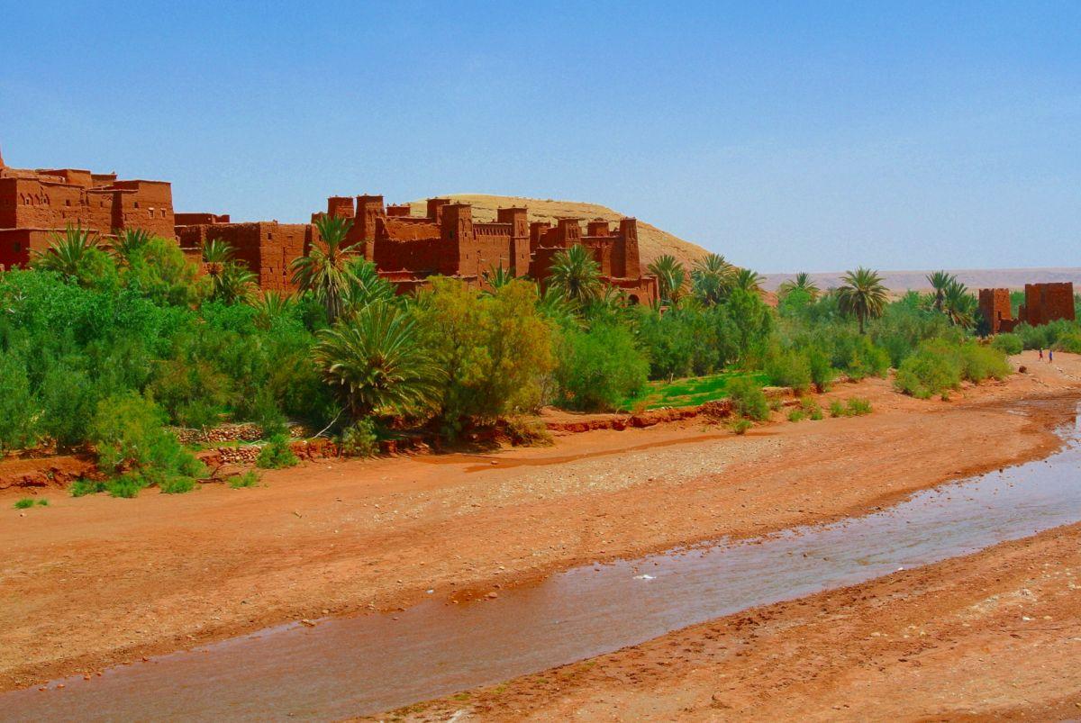 kleiner Bach, dahinter Reste einer Lehmburg in Marokko