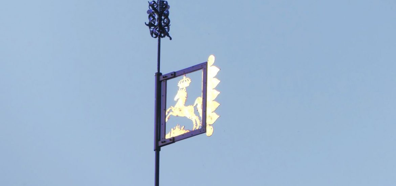 goldene Dachfahne vor blauem Himmel