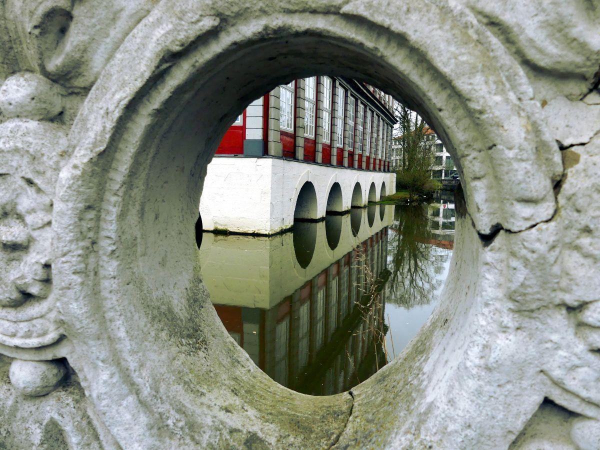Blick durch ein ovales Mauerfenster auf den Wassergraben