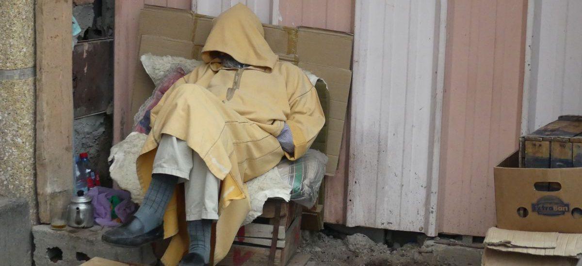 Mann schläft mit übers Gesicht gezogener Kapuze