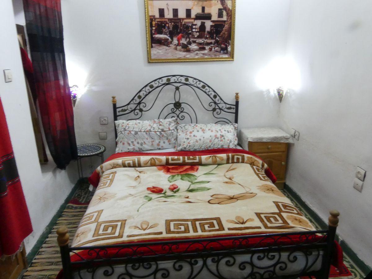 Bett mit Metallgitterrahmen, bunte Decke