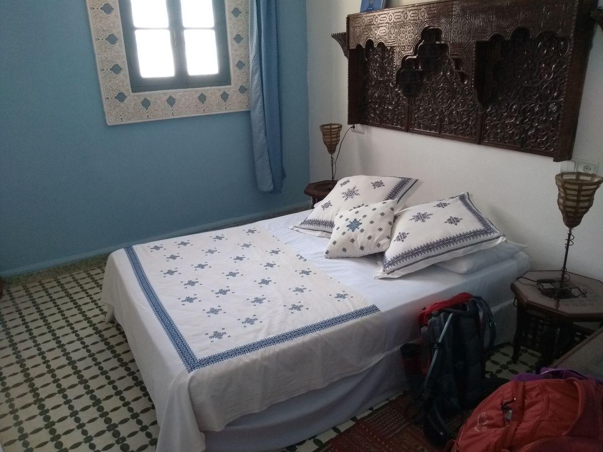 Doppelbett und hellblaue Wände, Fenster mit weißem Stuck umrahmt