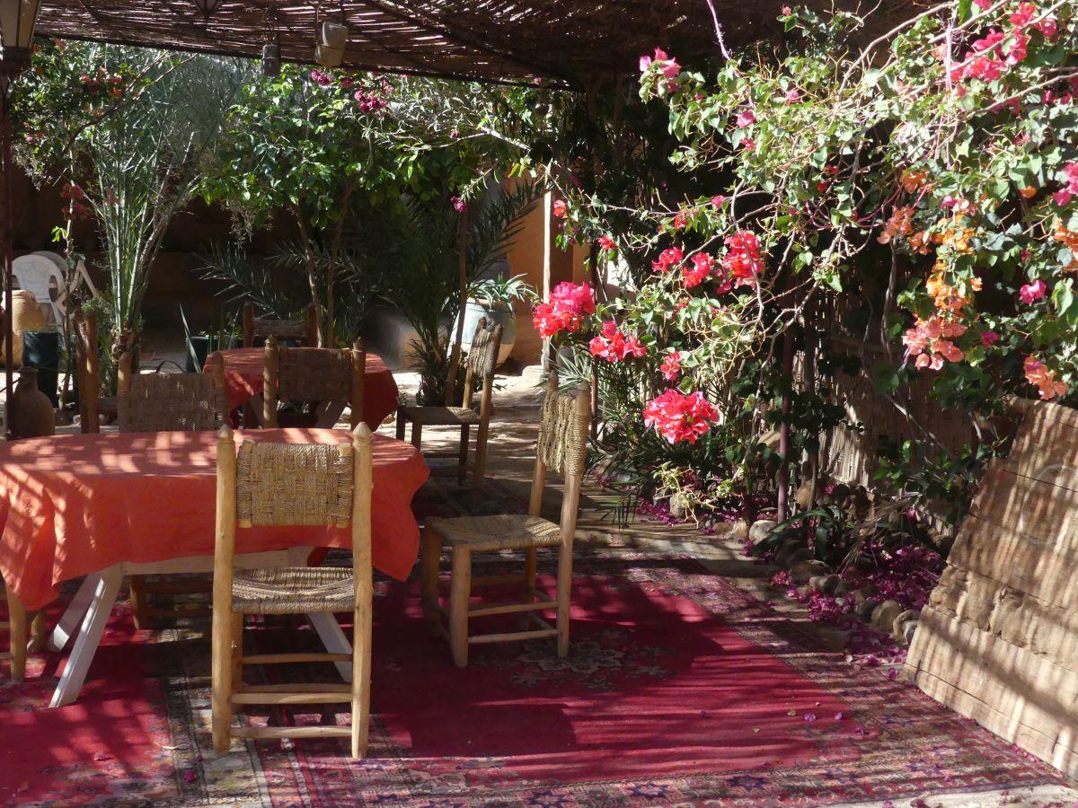 Tische und geflochtene Stühle unter blühenden Büschen
