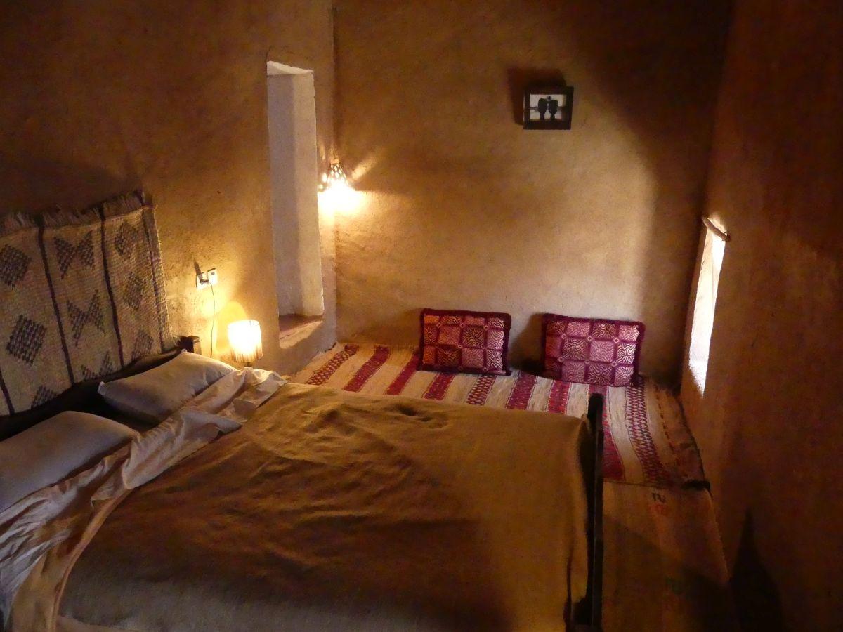 Zimmer mit Doppelbett, Teppichen und Kissen auf dem Boden