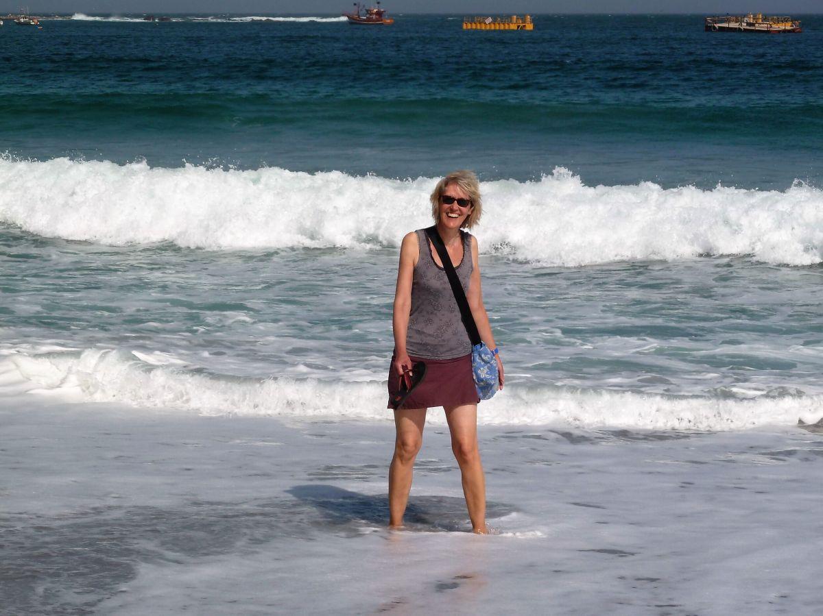 Gina steht in den Wellen am Strand