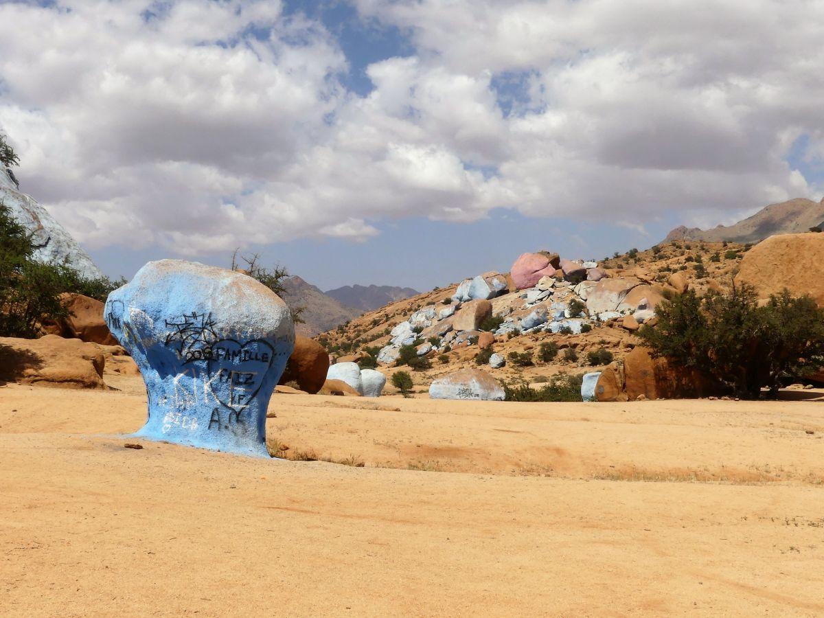 Leuchtend blauer Fels im Vordergrund, im Hintergrund ein Hang mit bunten Felsen