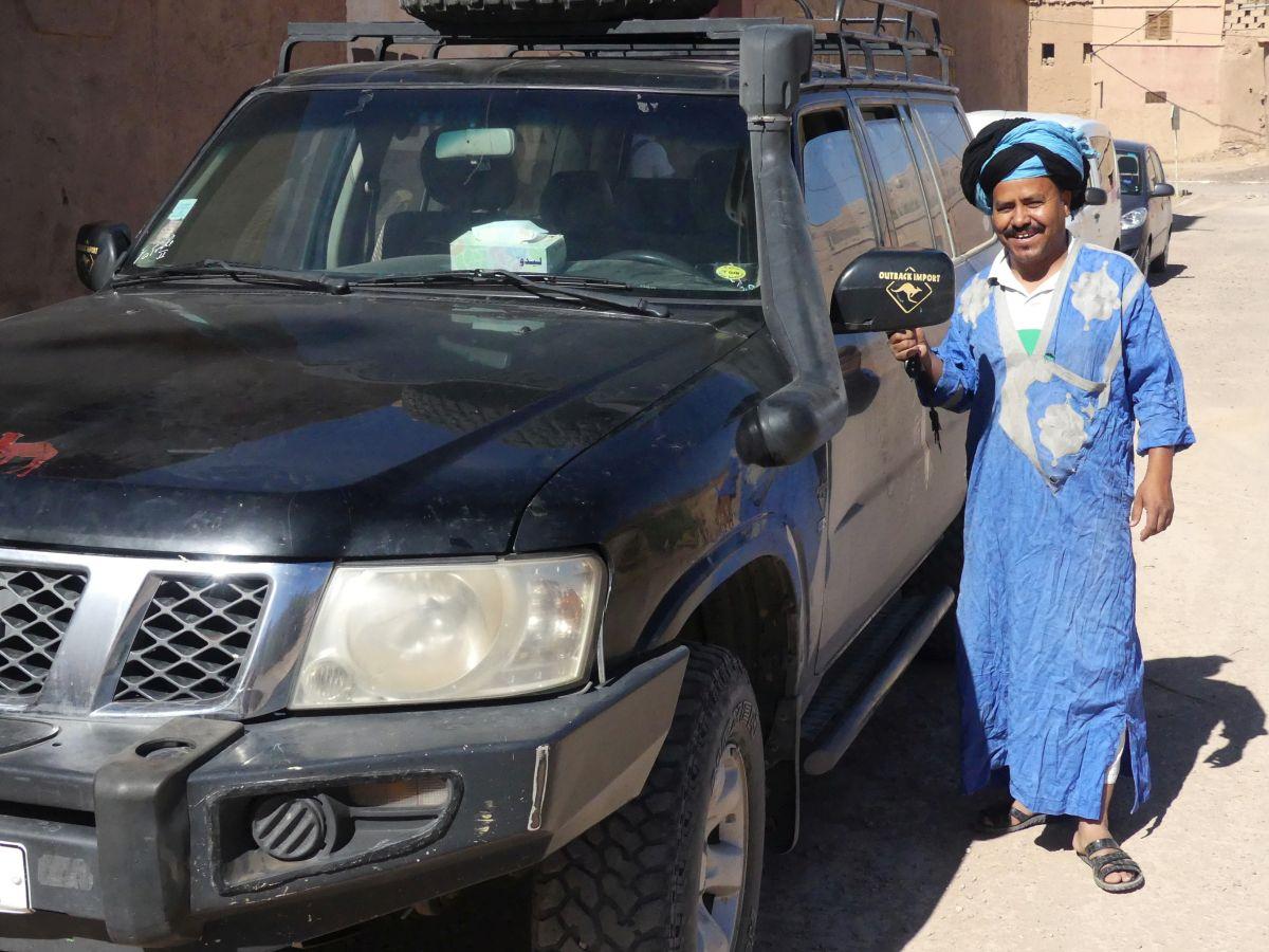 Blaugekleideter Berber vor schwarzem Geländewagen vor dem Start zur Wüstentour Marokko