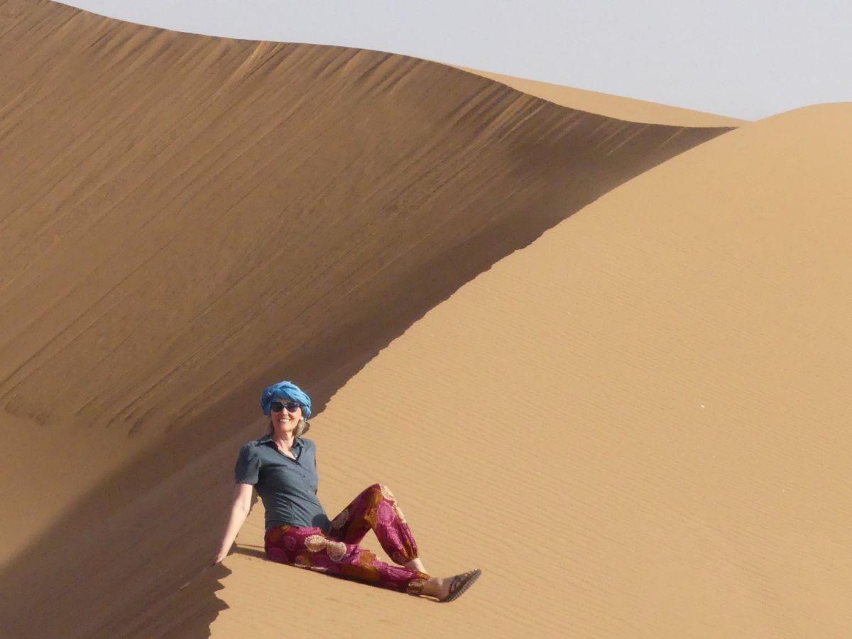 Gina sitzt auf der Düne auf unserer Wüstentour