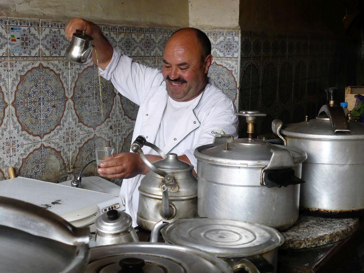 Koch schenkt Minztee ein