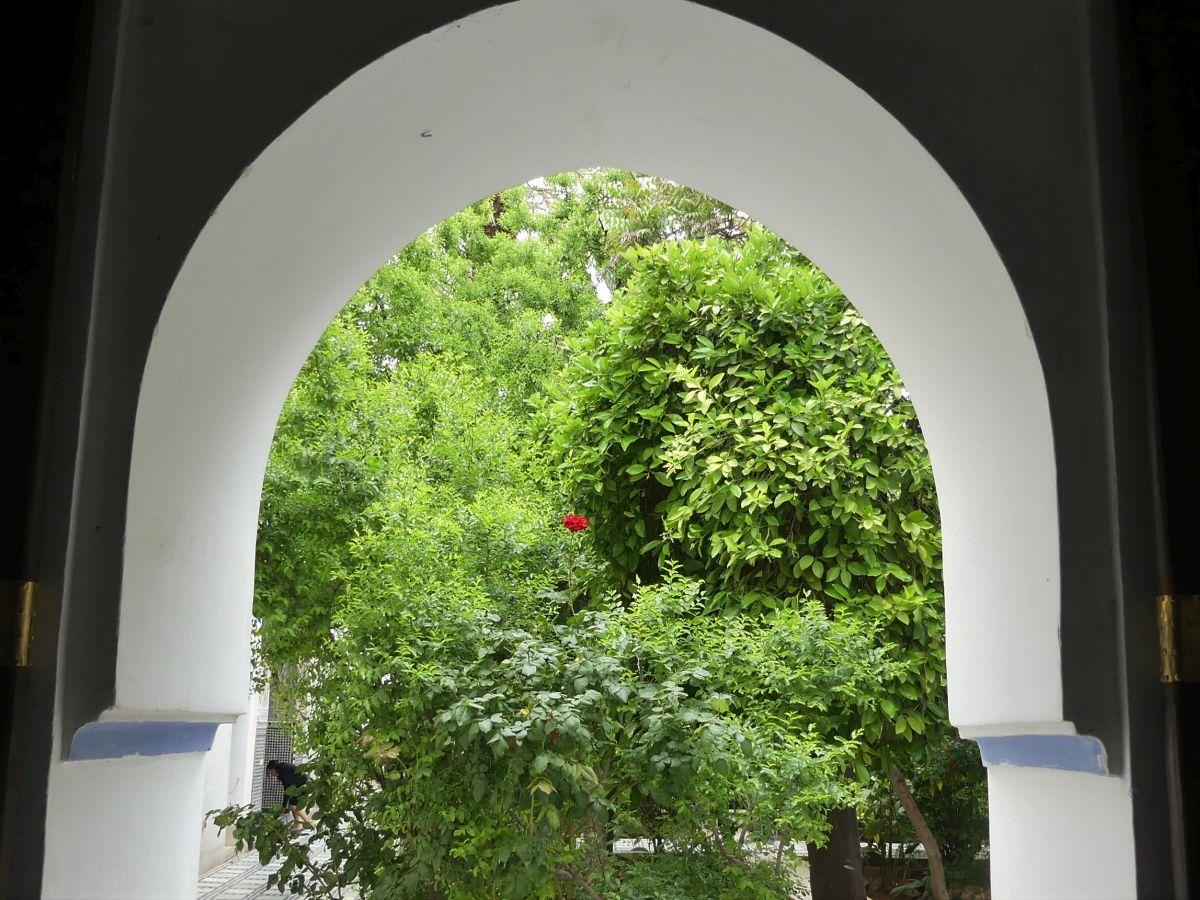 Blick durch einen Bogen ins Grüne