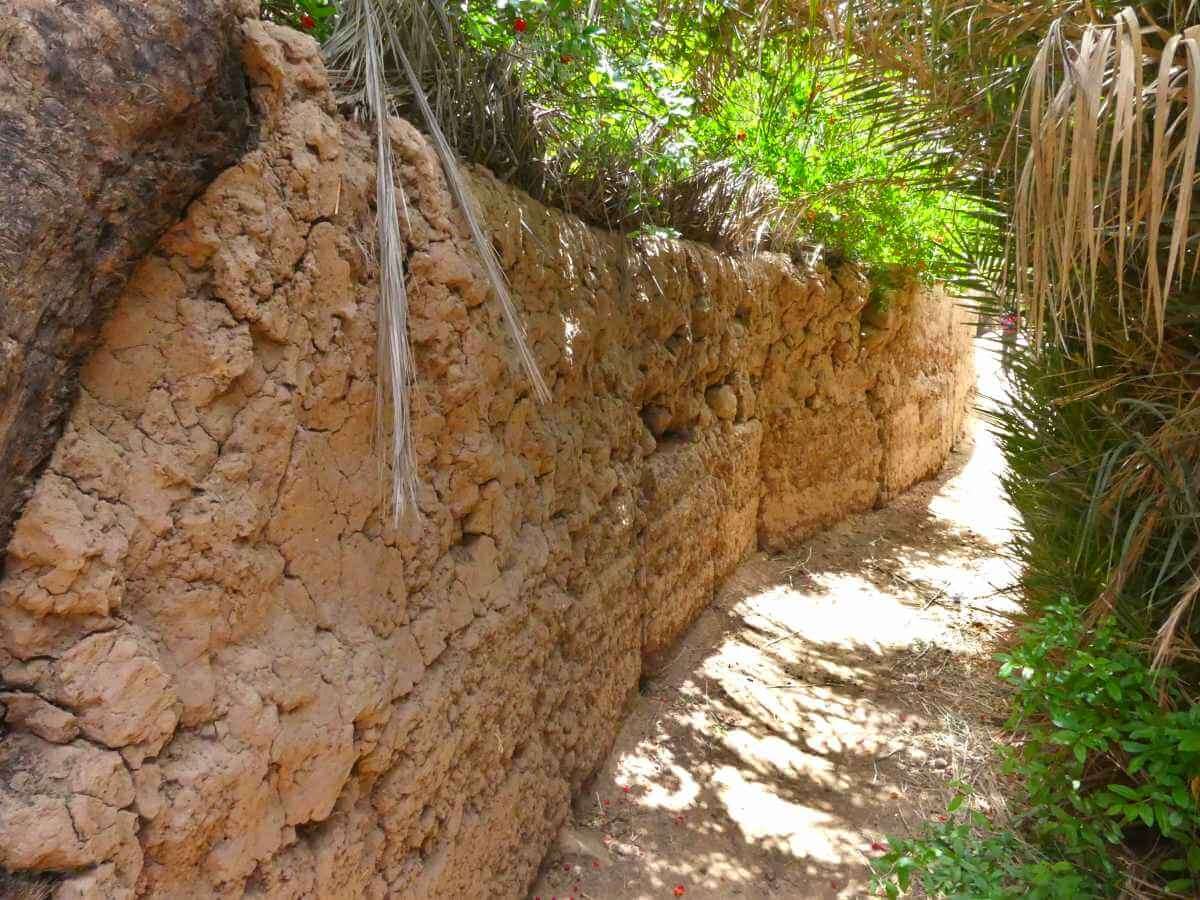 Schmaler Weg mit Lehmmauer an der Seite.