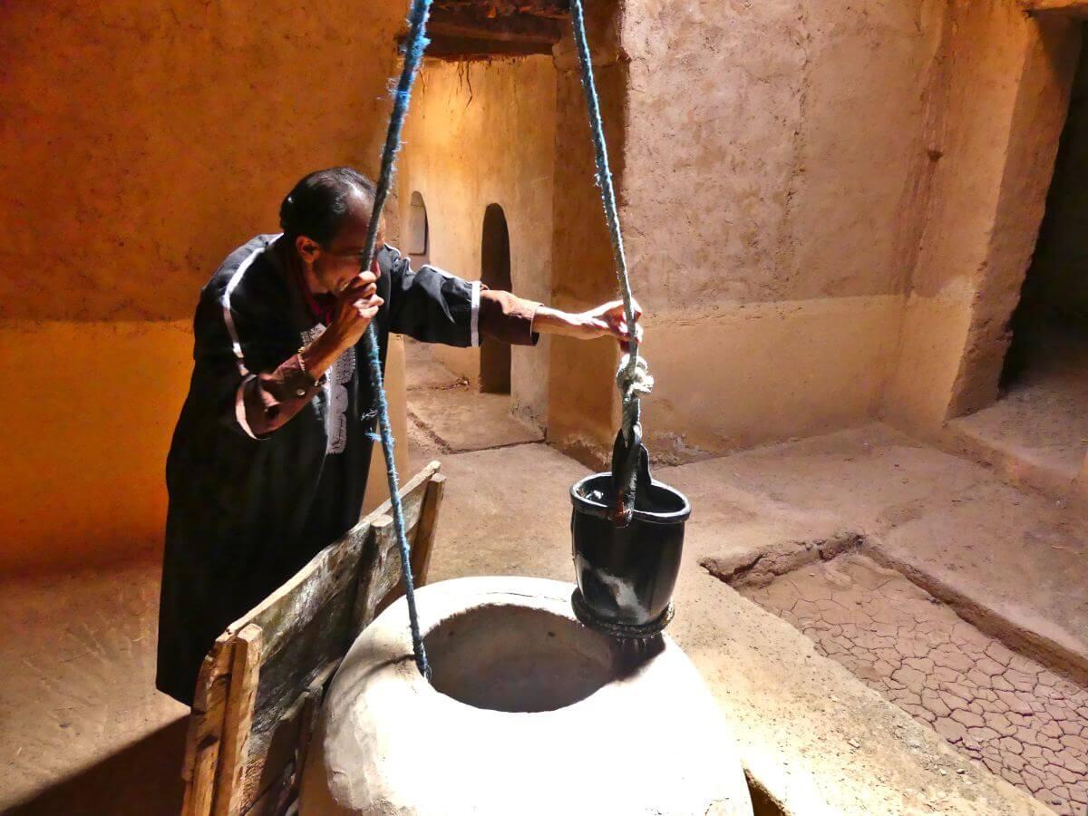 Mann zieht am Seil des Brunnens.