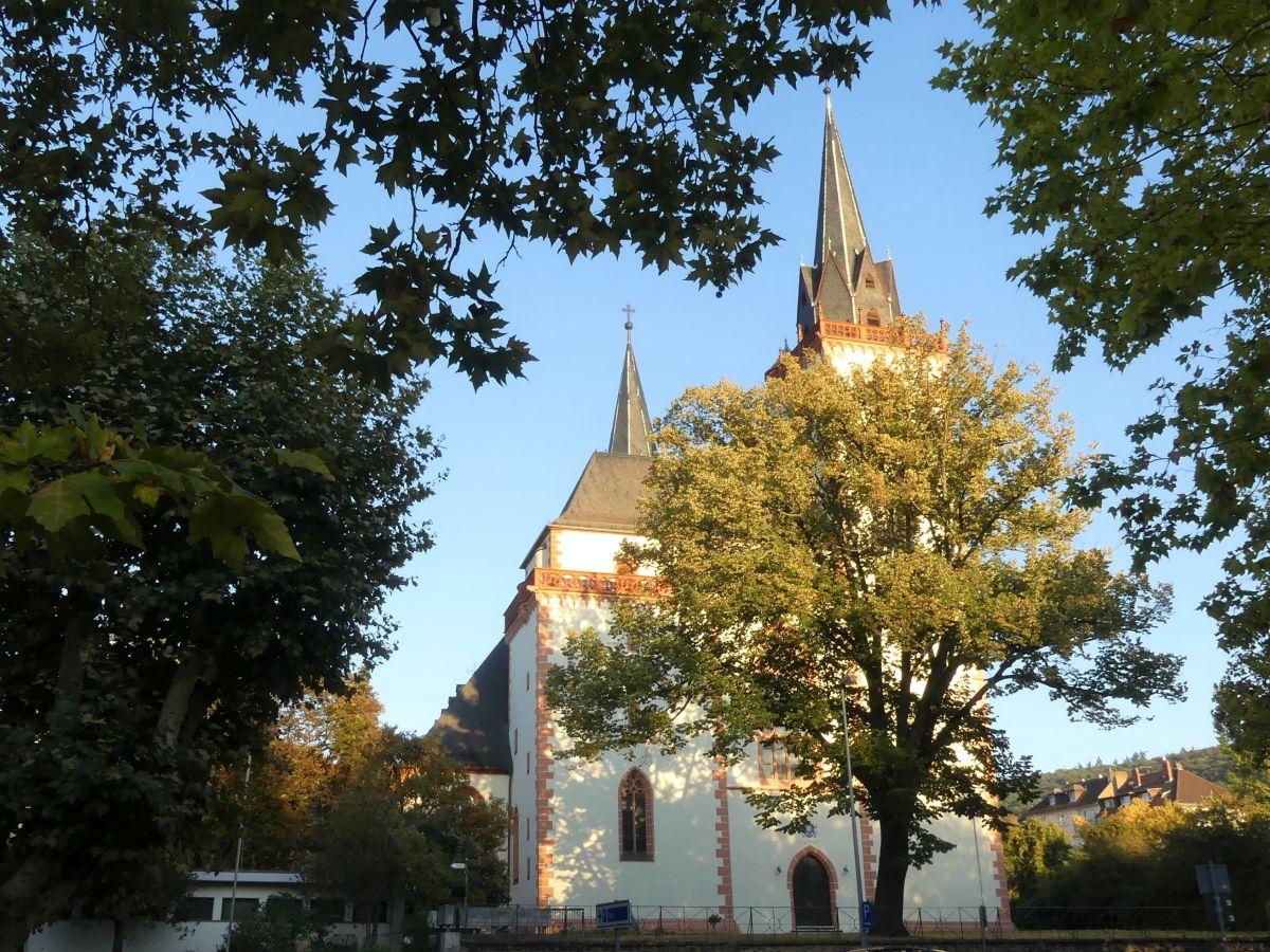 rot-weiße Kirche mit großem Baum davor.