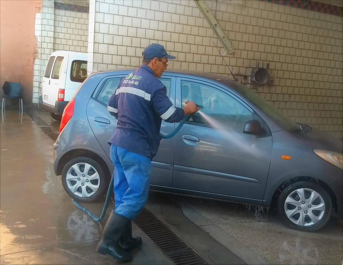 Mitarbeiter spritzt mit Schlauch das Auto ab