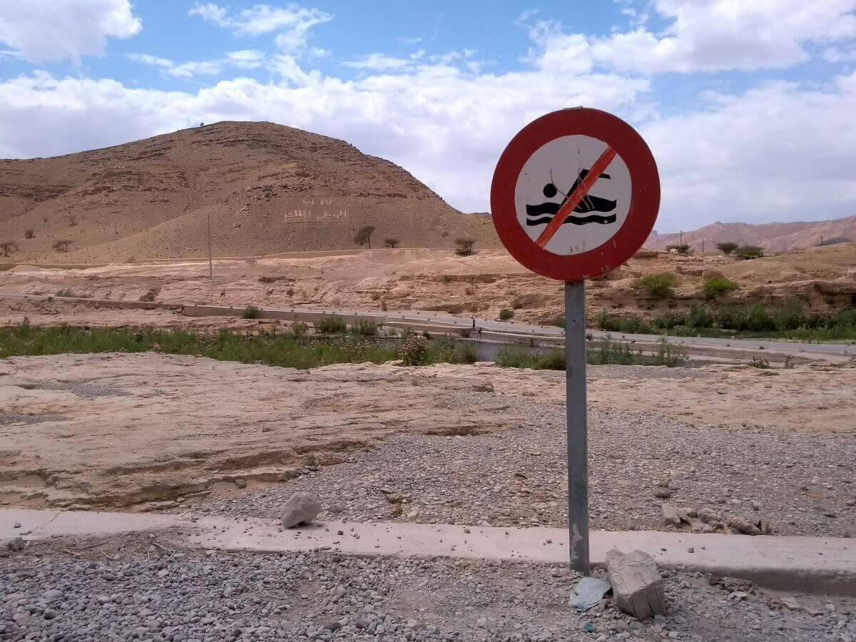 """Verbotsschild """"Nicht schwimmen"""" in der Wüste"""