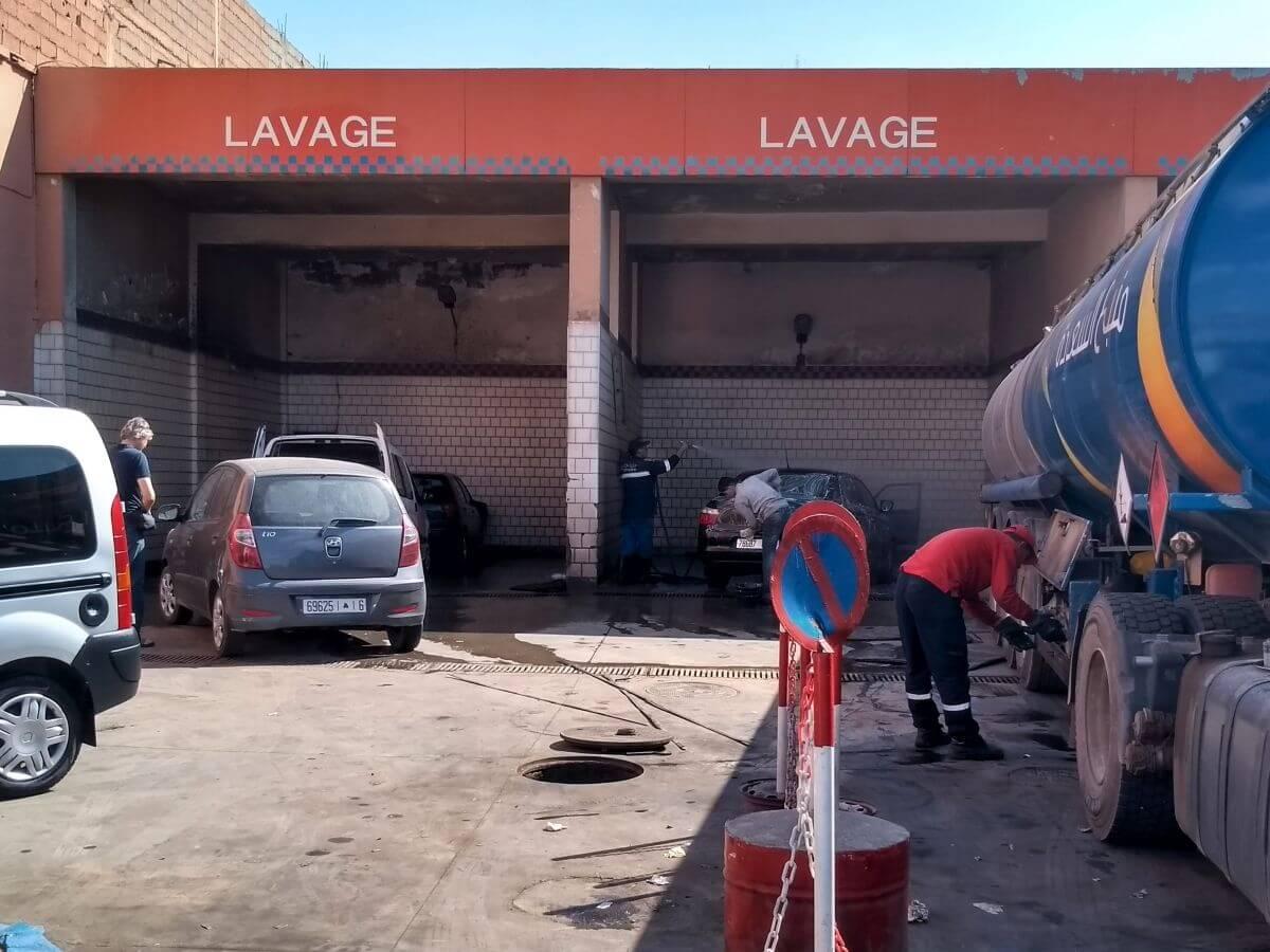 Staubiges Auto vor Waschanlage, daneben Tanklaster