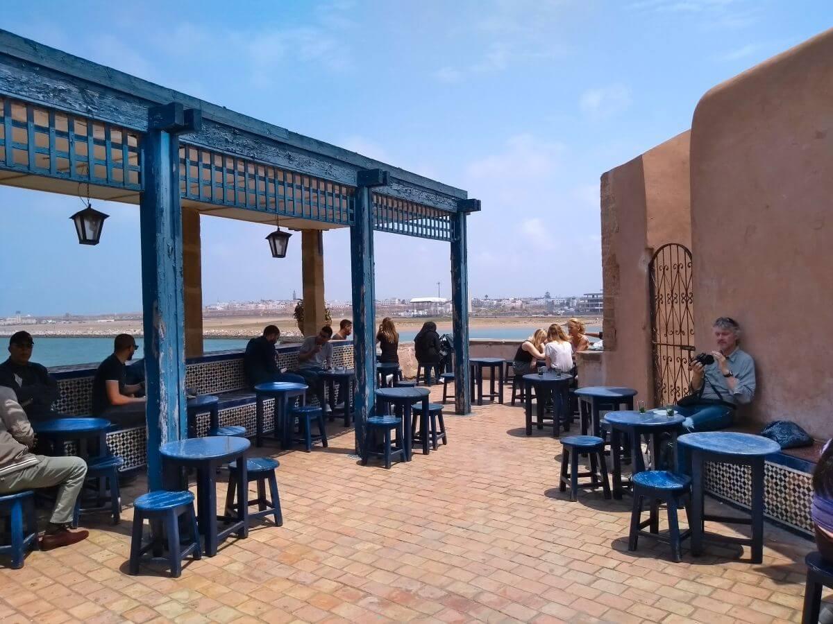 Blaue Tischchen und Hocker auf der Terrasse des Cafés