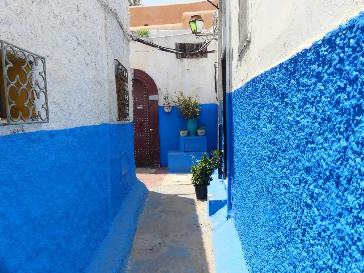 Schmale Gasse mit blau und weiß gestrichenen Häuserwänden