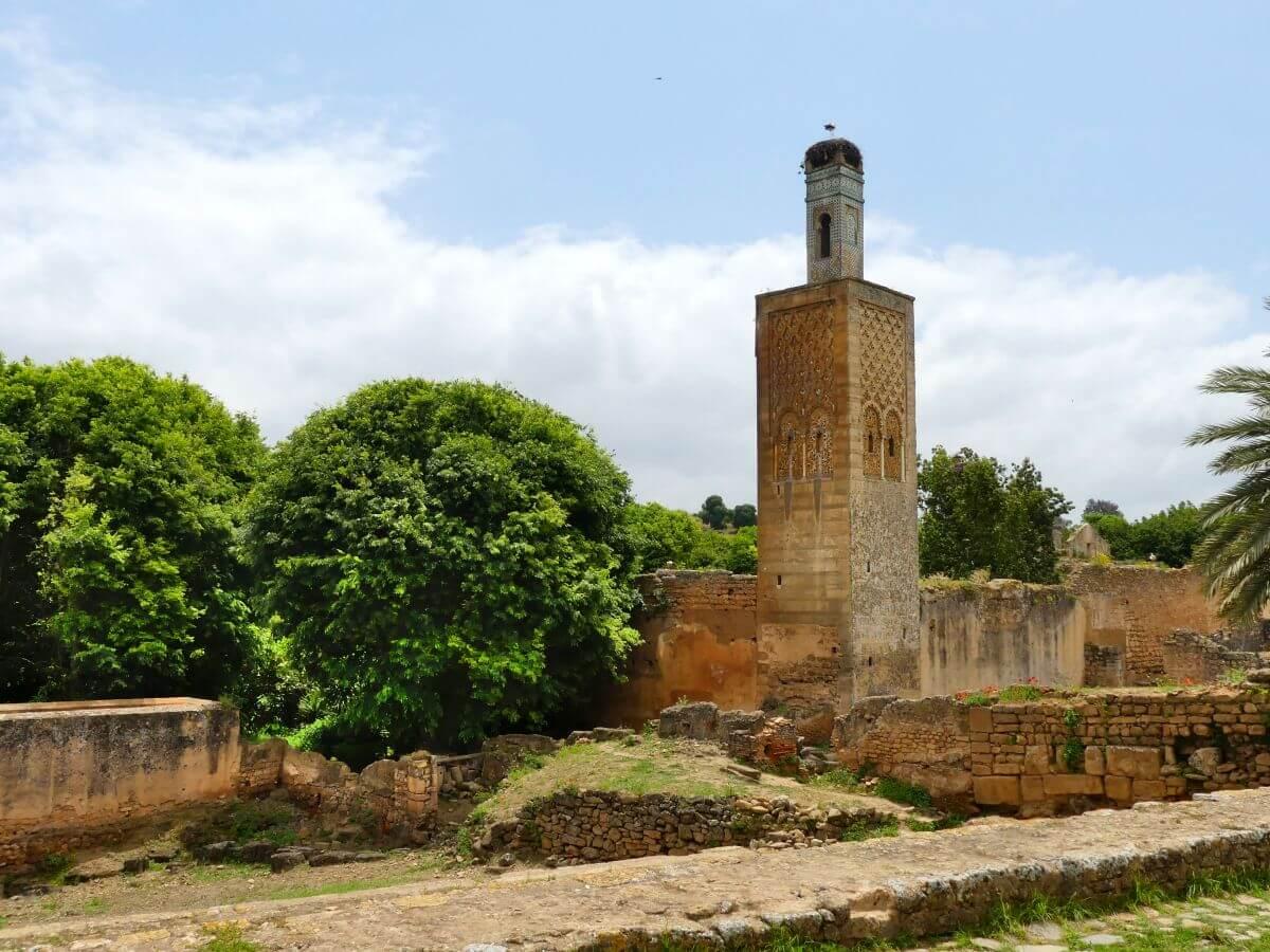 Turm einer Moschee zwischen Ruinen und Bäumen
