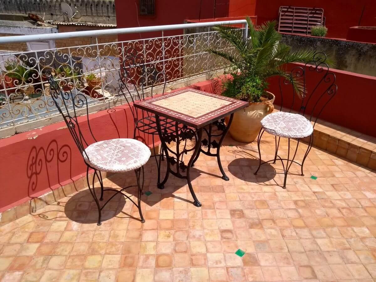 Kleiner gefliester Tisch und zwei Eisenstühle
