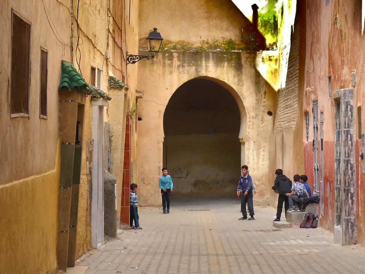 Ein paar Jungen spielen vor einem Torbogen