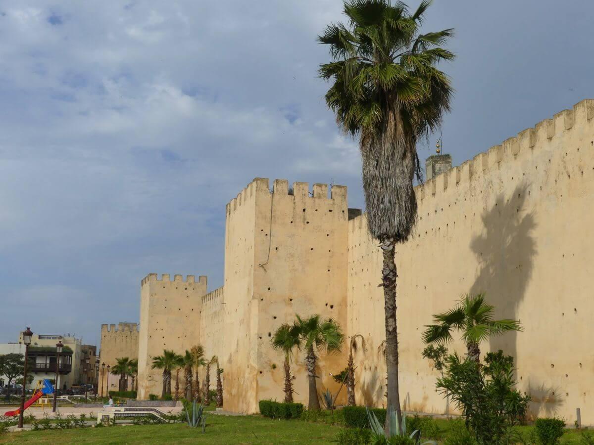 Hohe Stadtmauer mit viereckigen Türmen in Meknes