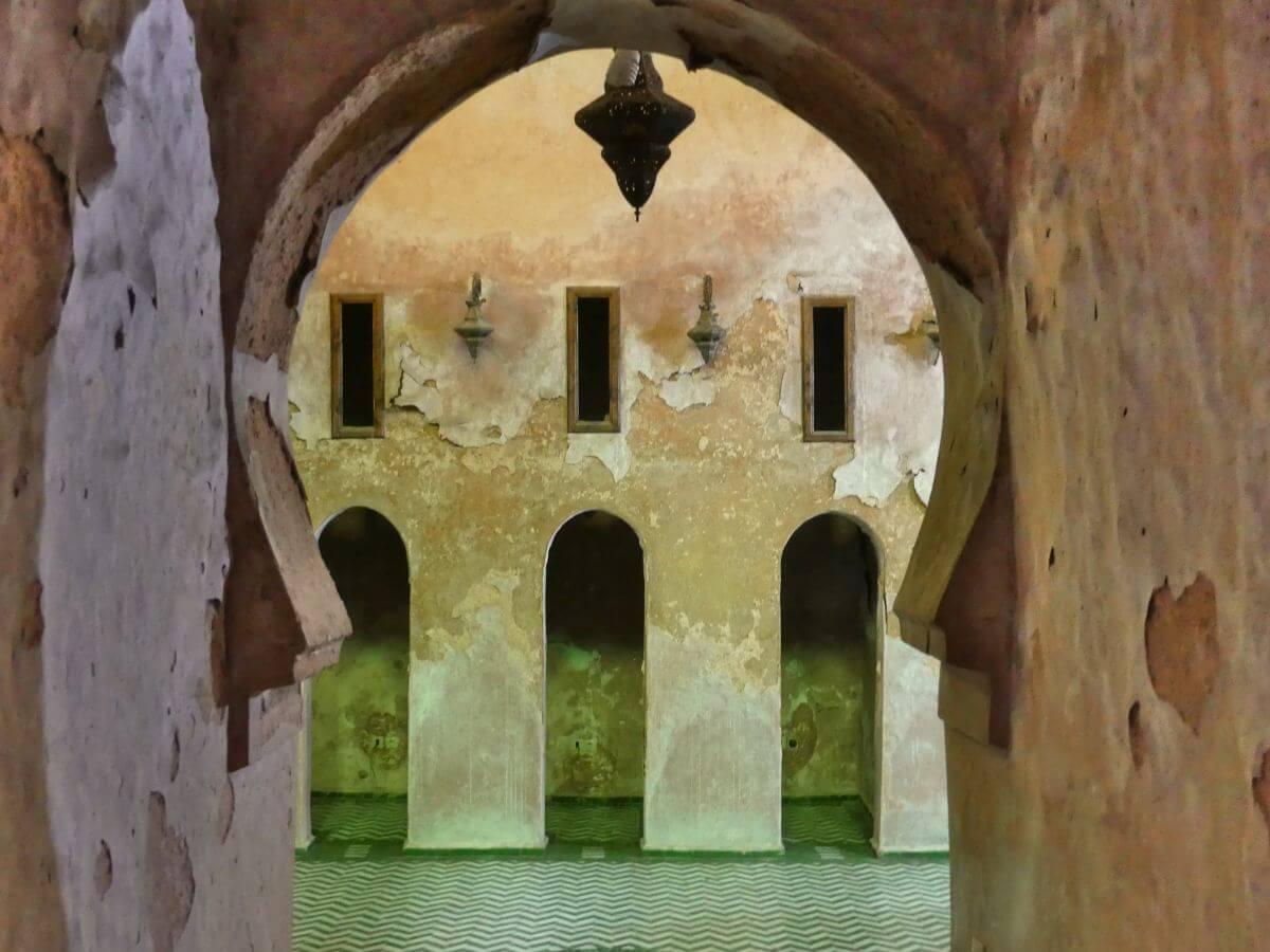 Maurischer Torbogen, dahinter großer Raum mit abblätterndem Putz