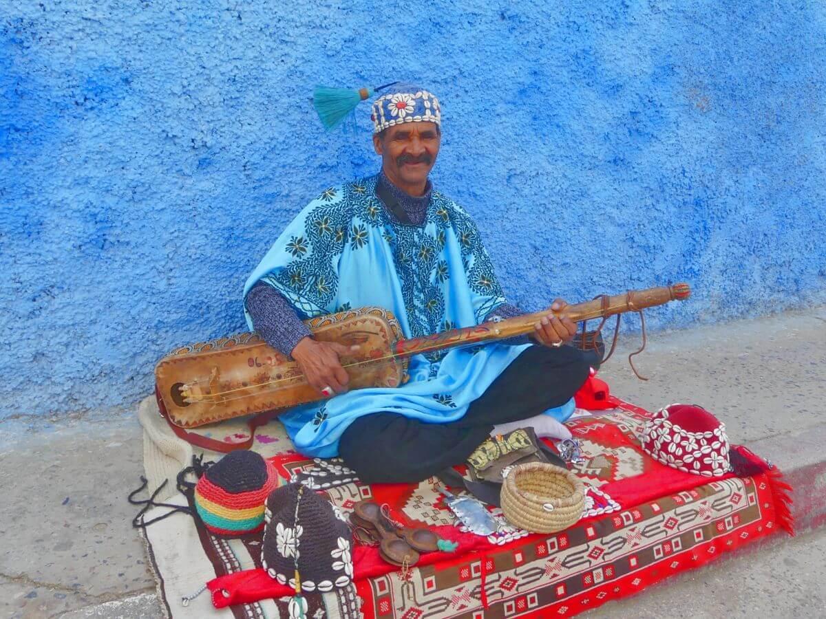 Mann mit Saiteninstrument sitzt auf Teppich auf der Gasse