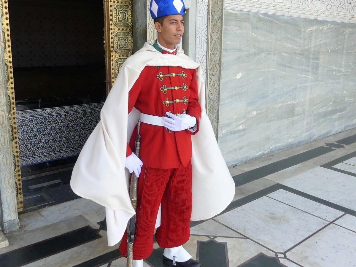Junger Mann in roter Uniform mit weißem Umhang