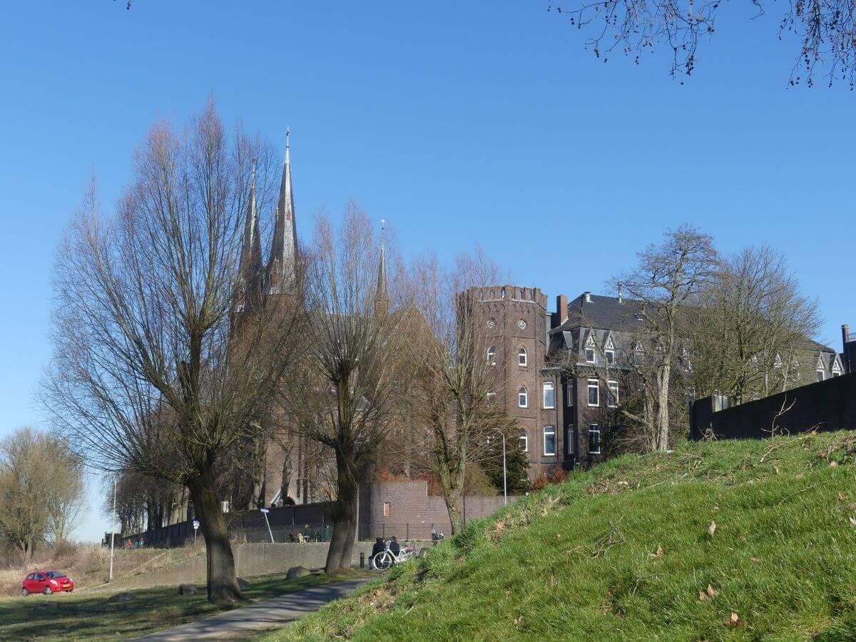 Kloster und Kirche hinter kahlen Bäumen an der Maas