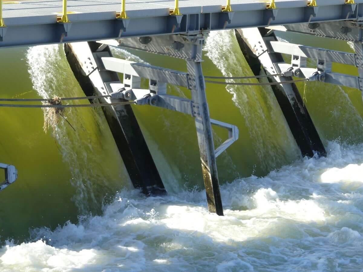 Wasser strömt schäumend durch die Wehrklappen