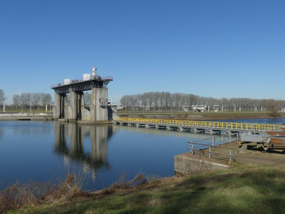 Wehrkante und große Stau-Tore hinter glatter Wasserfläche