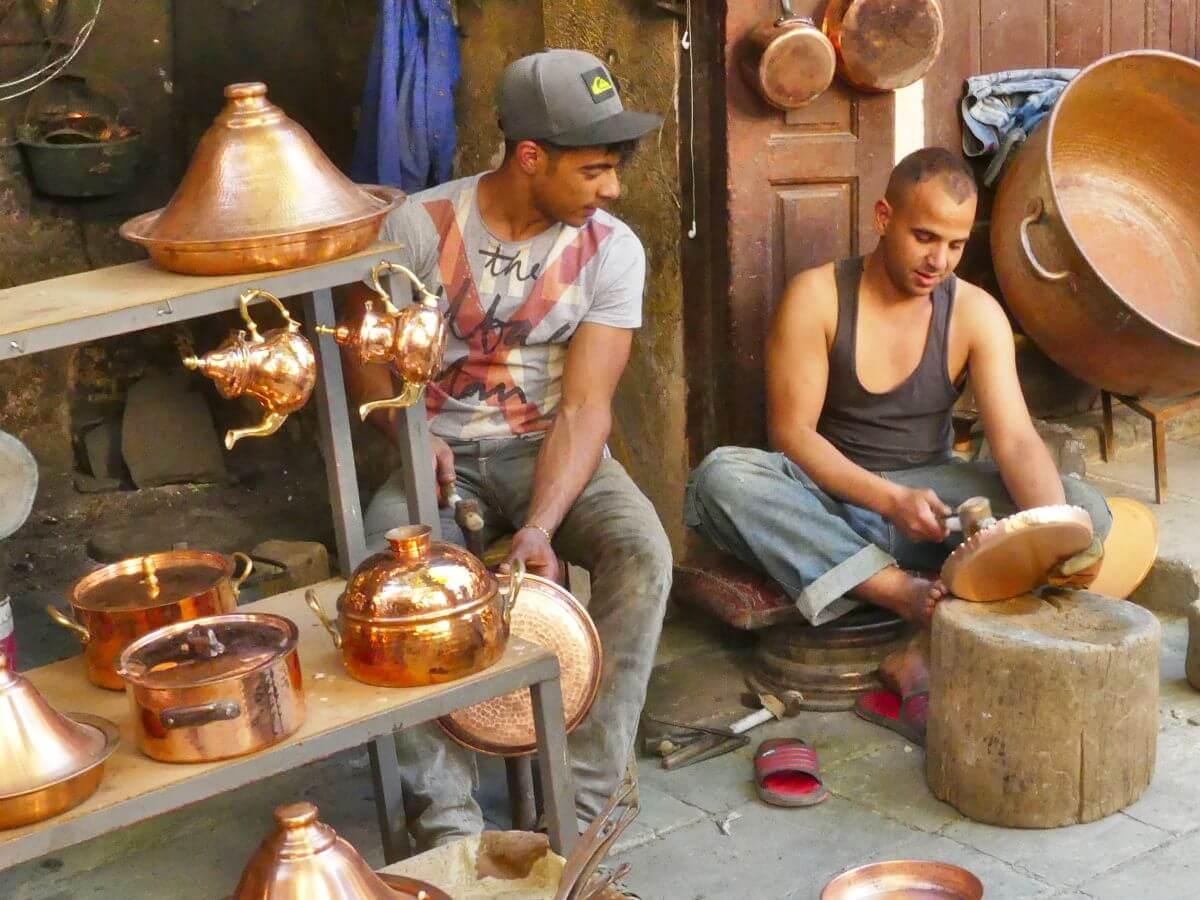 Zwei Handwerker hämmern auf Kupferstücke ein.